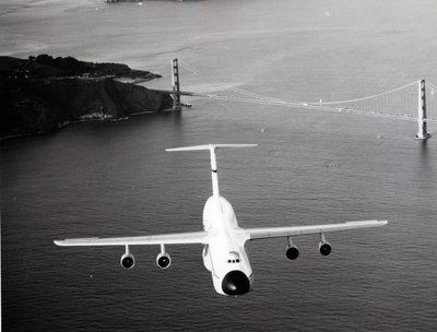 Een Lockheed C-5A Galaxy transportvliegtuig vliegt over de Golden Gate brug
