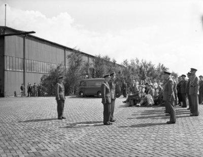 Opname van de plechtigheden op de vliegbasis Woensdrecht waar op 26 augustus 1958 het commando over de vliegbasis zal worden overgedragen door commodore-waarnemer W. de Toom           aan kolonel-vlieger W. Bakker. Tevens zal op deze dag de beëdiging plaatsvinden van 17 officieren.Op de foto in het miden kolonel-vlieger W. Bakker en commodore W. den           Toom. Rechts generaal-majoor-waarnemer H.P. Zielstra.