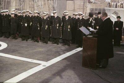 Indienststelling Hr.Ms. Van Galen (1967-1978). De ceremonie wordt geleid door kapitein-luitenant ter zee (kltz) F.H. Heckman, de 1e commandant van Hr.Ms. Van Galen. Alle           hens en de hoogwaardigheidsbekleders staan aangetreden op het helikopterdek. De voorzitter van de Schelde Directie, de heer J.W. Hupkes, houdt een toespraak. 5e van rechts (met bril),           vice-admiraal (vadm) A.H.J. van der Schatte Olivier, bevelhebber der zeestrijdkrachten (BDZ). 6e van rechts, vice-admiraal (vadm) H.M. van den Wall Bake, vlagofficier materieel. 7e van           rechts, schout-bij-nacht jonkheer W.C.M. de Jonge van Ellemeet, commandant der zeemacht in Nederland (CZMNed).