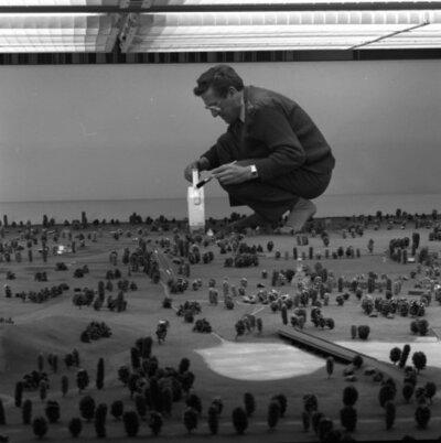Een medewerker van het Pantser Infanterie Rij Opleiding Centrum (PIROC) reinigt met een kruimeldief en een kwast de door de Centrale Werkplaats Instructiemiddelen van de           Koninklijke Landmacht vervaardigde maquette van de rijsimulator.<br>