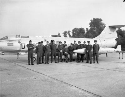 Groepsfoto van Starfighter-vliegers van het eerste uur voor de Lockheed RF-104G Starfighter D-8103.Van links naar rechts: elt.Vierdag, elt. Klijn, elt. Schuckman,           kpt.Adriaens, maj. Van de Spek, tlt. Groeneveld, elt. Heijboer, tlt. Schuur, elt. J. de Jong, elt. Koot, kpt. W. de Jong, tlt. De Kolf, kpt. Benneker en elt. Van Leeuwen.