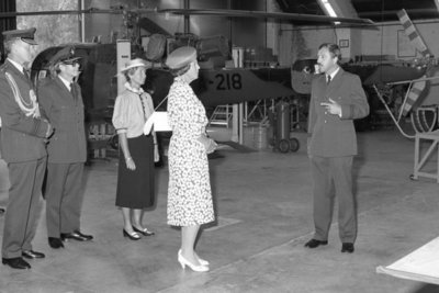 H.M. Koningin Beatrix tijdens een werkbezoek aan het Depot Vliegtuig Materieel (DVM) op de vliegbasis Gilze-Rijen. Geheel links kolonel R.M. van der Baan, commandant DVM en           geheel rechts kapitein J.Rus, hoofd kantoor Technisch Onderzoek DVM.