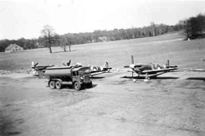 Drie Spitfire LF.Mk.IX's van de Jachtvliegschool (JVS) op de lijn met daarvoor een tankwagen. Het middelste toestel is de H-1.
