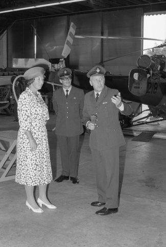 H.M. Koningin Beatrix tijdens een werkbezoek aan het Depot Vliegtuig Materieel (DVM) op de vliegbasis Gilze-Rijen. In het midden kolonel R.M. van der Baan, commandant DVM en           rechts adjudant-onderofficier A. Goethals, hoofd afdeling Helicopteronderhoud.