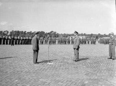 Opname van de plechtigheden op de vliegbasis Woensdrecht waar op 26 augustus 1958 het commando over de vliegbasis zal worden overgedragen door commodore-waarnemer W. de Toom           aan kolonel-vlieger W. Bakker. Tevens zal op deze dag de beëdiging plaatsvinden van 17 officieren. Achter de microfoon commodore Den Toom en in het midden kolonel           Bakker.