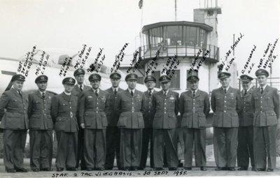 Groepsfoto van de Staf van 2TVB (2e Tactische Vliegbasis Eindhoven) op 30 september 1955.V.l.n.r.: Kapitein-J.B.W.M. de Koning (kapitein-adjudant C2TVB),           majoor-vlieger-waarnemer U. Scipio (commandant 2 Tactische Basis Groep), majoor Gruyters (aalmoezenier), majoor H.J.G. Stieglis (commandant 2 Tactische Onderhoud en Bevoorrading Groep),           luitenant-kolonel-vlieger-waarnemer L.W. Hansen (commandant 2 Tactische Jachtgroep), luitenant-kolonel-vlieger J.P. Kuijpers (chef staf), kolonel-waarnemer H.P. Zielstra (commandant 2 TVB),           majoor J. de Ronde (hoofd Squadron- en Periodiek Onderhouds Squadron), majoor Bartlema (dominee), majoor-vlieger-waarnemer B.E. de Smalen (hoofd Sectie Operatiën), luitenant Verstappen           (OVD) en kapitein R.F. van Hoof (Bedrijfsbureau 2TVB).