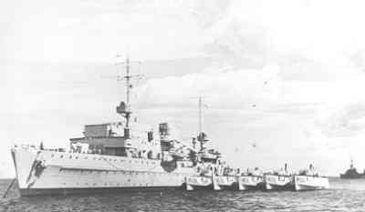 Het Duitse depotschip Tanga (1938) voor anker liggend, van bakboordzijde gezien, met langszij 5 motortorpedoboten.