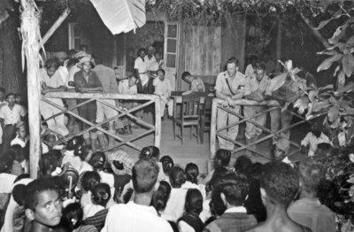 Netherlands Indies Civil Administration functionarissen worden tijdens hun werkbezoek aan Timor verwelkomd in het dorp Seo. De inwoners van Seo hebben zich voor de veranda           verzameld en slaan op gongs ter ere van de bezoekers.
