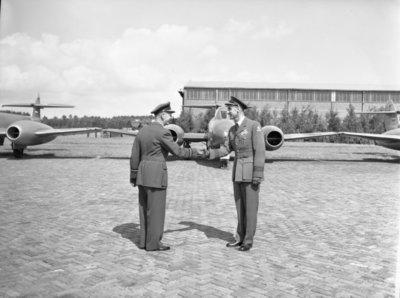 Opname van de plechtigheden op de vliegbasis Woensdrecht waar op 26 augustus 1958 het commando over de vliegbasis zal worden overgedragen door commodore-waarnemer W. de Toom           aan kolonel-vlieger W. Bakker. Tevens zal op deze dag de beëdiging plaatsvinden van 17 officieren.Op de foto felicitaties van commodore Den Toom aan kolonel Bakker. Op de           achtergrond Gloster Meteor straaljagers.