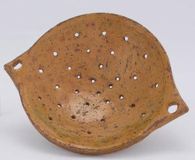 Een aardewerken vergiet, lichtbruin en geelgroen