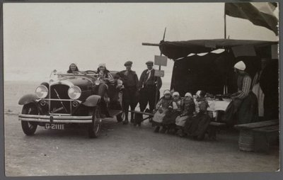Gezicht op gezinnen in klederdracht met o.a. een Marmon automobiel