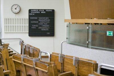 Interieur, overzicht van de veilingzaal met informatiebord aan de muur
