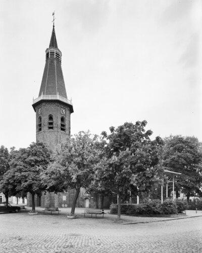 Kerktoren, muziektent op kerkplein, omgeven door bomen