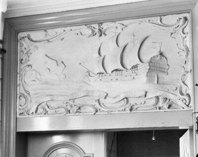 Bovendeurstuk van stucwerk in de hal bij het trappenhuis