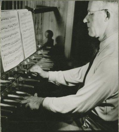 De bekende beiaardier Ferdinand Timmermans achter de speeltafel van het carillon in de toren van de Grote of St. Janskerk in 1949.