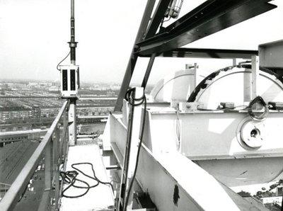 Waarschijnlijk bovenin het boorschip Petrel op de werf van IHC Gusto. Op de achtergrond is de wijk De Gorzen te zien. De Petrel zelf kon na de bouw zonder hulp van ankers           naar olie en gas boren. De Petrel is op 6 september 1975 te water gelaten en de doop is verricht door mevrouw Didier, de vrouw van de directeur van ELF uit Parijs. Het schip heeft 140           miljoen gulden gekost. Bouwnummer 947.