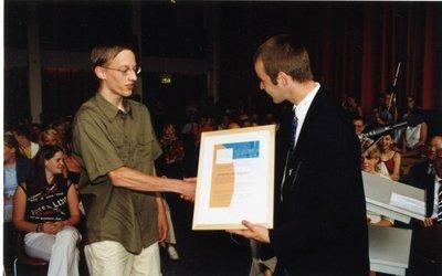 Op de dag van de uitreiking van de einddiploma's op sg. Spieringshoek (27 juni 2003) ontvangt Johan Westerveld (5 Havo) uit handen van docent H.J.J. Noordam een oorkonde           wegens bijzonder resultaat voor het vak scheikunde of natuurkunde.
