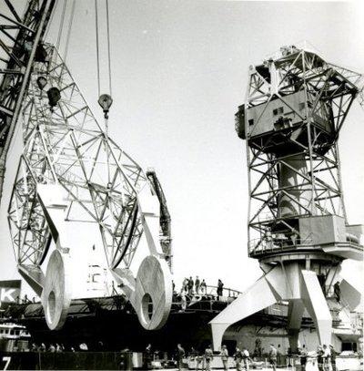 Plaatsing van vlucht op toren (40 tons wipkraan, kraan no 41 /349) door bok Titan. Plaats kade stuurboordzijde dok 7. Op de achtergrond Hr. Ms. Karel           Doorman.