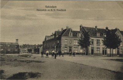 De Havendijk met een aantal panden (rechts) en de Havenstraat (links) . In laatstgenoemde straat een r.k. noodkerk. Op de voorgrond links de plek waar in de jaren 1916-1926           noodwoningen stonden voor bewoners van de Noorderstraat (de zgn. Rooiekoolbuurt) ten noorden van het NS-station. De woningen daar waren zó slecht dat ze afgebroken moesten worden en de           bewoners tijdelijk werden ondergebracht in de genoemde noodwoningen. Zie de Schiedamse Corant van o.a. 12 juli 1916