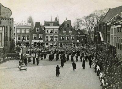 Opmars van het Stedelijk Muziekkorps naar het versierde stadhuis tijdens de feestelijkheden ter gelegenheid van de geboorte van prinses Beatrix. In de Lange Kerkstraat staat           een erepoort, een afspiegeling van de Rotterdamse Poort.