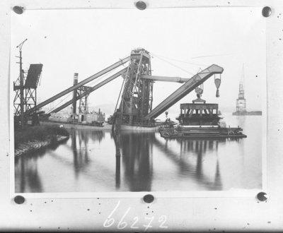 Zijaanzicht van een 250 ton drijvende kraan (Bnr. 716), getiteld de Manchester Ship Canal, met als bestemming het Manchester Shiping Canal Company. De kraan is ontworpen           door ingenieur Viktor Gerosa en gebouwd bij Werf Gusto, Firma A.F. Smulders. De kraan moest drie functies vervullen: 1) het plaatsen en transporteren van sluisdeuren; 2)           bergingswerkzaamheden en 3) laden en lossen van zware lasten in schepen. Fotonummer in het E-depot: 0386-482-004
