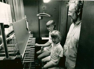 Beiaardier Addie de Jong met zijn kinderen achter de carillontafel van het orgel van de Grote of St. Janskerk.