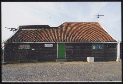Zaandam. Kalverringdijk. Onttakelde mosterdmolen De Huisman, Kalverringdijk 23. Eigenaar Vereniging De Zaansche Molen. De Huisman is een kleine achtkante stellingmolen. Hij           staat sinds 1955 op het pakhuis De Haan. In januari 2010 is men begonnen met de verbouwing van De Huisman. De moderne mosterdmakerij in de molen werd verplaatst naar een industrieterrein in           Wormerveer. Naast het pakhuis De Haan is een nieuw deel gebouwd waarop het achtkant in december 2010 geplaatst is. In dit nieuwe gedeelte staan 3 koppels kantstenen die zowel elektrisch als           met windkracht aangedreven kunnen worden. Het pakhuis De Haan heeft een nieuwe fundering gekregen en is 30 cm omhoog-gebracht. In dit pakhuis kwam een specerijenwinkel. 16 september 2011           heeft Z.K.H. Prins Friso als Beschermheer van De Hollandsche Molen het complex officieel in gebruik gesteld.