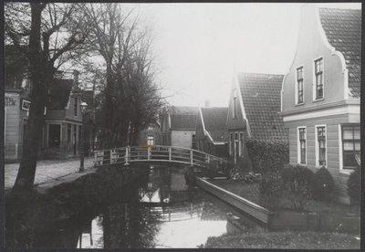 Koog aan de Zaan. Raadhuisstraat. Gezien in zuidelijke richting met rechts no. 17, noordhoek Julianastraat en links no. 20. Mantel Magazijn J. v Nugter.