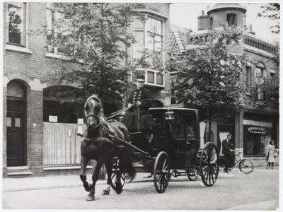 Zaandam. Czarinastraat. Centraal de toegang tot het Dampad. Op de achtergrond café Edelweiss. De bestuurder van de paardentaxi is Cees van Nek van Erven Jan de           Boer.