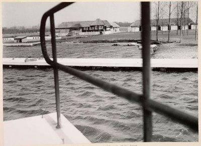Wijdewormer. Zuiderweg. Natuurbad Wijdewormer. Het zwembad gezien vanaf de springplank. Het natuurbad ontstond door een natuurramp in 1825, de dijk brak door en het land           raakte onder water. Tijdens de ramp ontstond een wiel oftewel een plas ook wel spoelgat genoemd op het terrein van boer Maarten Prins. De boer liet de mensen bij mooi weer voor een           dubbeltje zwemmen. Men kleedde zich om achter schotten van riet. Op 17 december 1953 werd besloten tot de aanleg van een natuurbad in de Wijdewormer in een bijeenkomst van           vertegenwoordigers van de Wijdewormer, burgemeester J.F. de Groot en vier Zaangemeenten, wethouder M.J.Hille van Zaandam, burgemeester L.A. Ankum van Koog aan de Zaan, wethouder D. Grin van           Wormerveer en burgemeester A.H. van Gelderen van Zaandijk. Het leidde tot vorming van de Stichting Natuurbad Wijdewormer. Deze kocht grond aan en er verrees aan de Zuiderweg een mooi           recreatiepark dat op 14 mei 1956 officieus werd geopend. De Officiële opening was op 31 mei 1956, door mr. dr. M.J. Prinsen, commissaris der koningin in de provincie Noord-Holland. In de           jaren zestig trad er een terugloop op, de grote boosdoener was de kwaliteit van het zwemwater door wieren. In het water bevonden zich slakken die de veroorzaker waren van leverbotziekte en           het wemelde er van de ratten die de ziekte van Weil over konden brengen. Het bad ging in 1986 dicht. In 1991 kwam er een golfbaan op het terrein. Zie het artikel van 11 april 1956 in de           Zaanlander.
