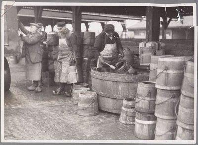 Zaandam. Westzanerdijk. Op de foto de heren Koops, Botterman, Roepert en Schoone aan het werk in de ontsmettingsloods. Ooit was de privaatton een moderne vervanging voor het           huisje aan de sloot. In 1874 was het tonnenstelsel ingevoerd en het zou bijna 100 jaar duren voordat de laatste ton was verdwenen. Eerst kwamen er de beerputten, daarna de waterclosets           (WC's). Aan de Westzanerdijk was de beerput gevestigd, waar de faecaliën werden gestort. Daarna werden de tonnen schoongemaakt en ontsmet met het middel Creolien.