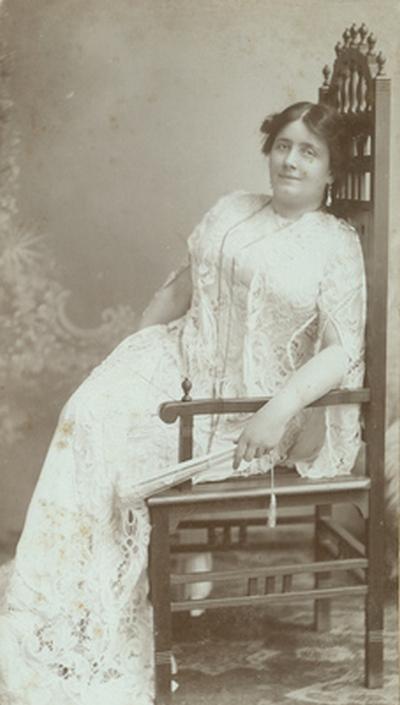 Lukács Júlia uszályos fehér csipkeruhában*, széken ülve, legyezővel (változat)