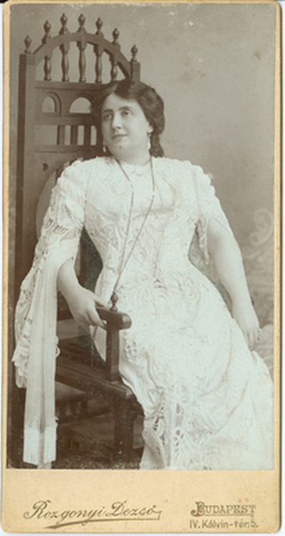 Lukács Júlia uszályos fehér csipkeruhában*, széken ülve szemben
