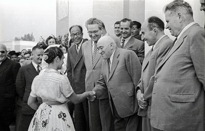 Népviseletbe öltözött nő kézfogása Rákos Mátyással