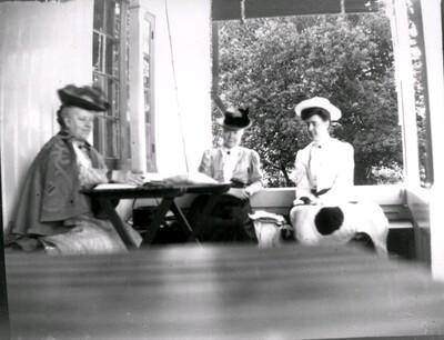 Tre kvinnor på veranda