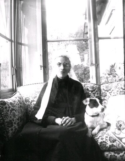 Äldre kvinna med hund på veranda