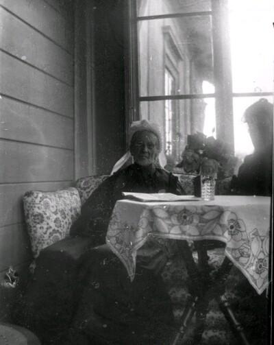 Äldre kvinna på veranda