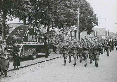 Het detachement van het 21e Regiment Infanterie onder commando van de reserve tweede luitenant G.H.H. Schröder op het parcours van 40 km onderweg op de tweede dag van de 28e Vierdaagse. Het passeert de reclameauto van