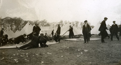 New recruits in civilian clothes erecting tents
