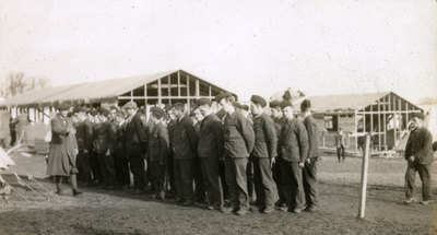 Men, some in uniform and some in civilian dress, outside half built in Heaton Park