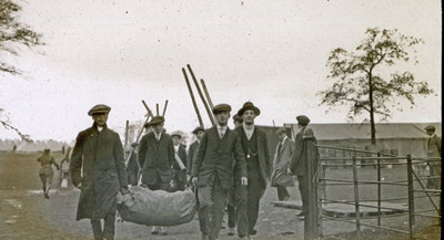 Group of men from the Pals Battalions carrying equipment for the erection of tents and hutments in Heaton Park