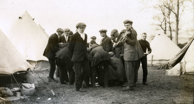 Group of men from the Pals Battalions, including one with a violin, at leisure amongst tents in Heaton Park