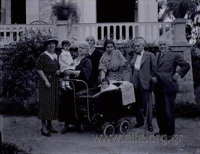 Οικογενειακό πορτραίτο. Από αριστερά η Άσπα Πετροκοκκίνου σύζυγος Δημητρίου, η Μαρία Εμπεδοκλή το γένος Πετροκοκκίνου σύζυγος του Γρηγορίου Εμπεδοκλή κρατά τη μικρή Μαρία Παπατσώνη, πίσω της η Λιλή Βαφιαδάκη το γένος Ζερβουδάκη μητέρα του φωτογράφου, στο κέντρο η Σεμίρα Βαφιαδάκη το γένος Εμπεδοκλή, σύζυγος Παντελή Βαφιαδάκη, δίπλα της με το παιγιόν ο Κωνσταντίνος Ζερβουδάκης (Ντιντής) αδελφός της Λιλλής, και δίπλα του ο Αντώνης Βαφιαδάκης, πατέρας του φωτογράφου. Στο καρότσι η μικρή Λιλή Βαφιαδάκη κόρη της Σεμίρας.
