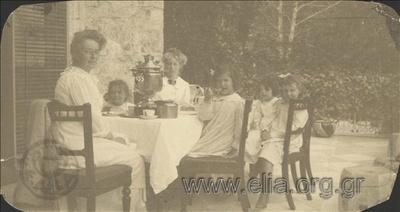 Ο Νικόλας Κάλας (1907-1988), παιδί, με τις πριγκίπισσες Μαρία, Ελισάβετ και Όλγα σε τραπέζι βεράντας.