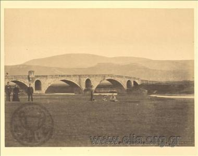 H πέτρινη γέφυρα του Ενιπέα (Τσιναρλή), στο βάθος τα Φάρσαλα και η Ακρόπολη.