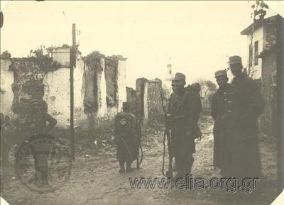 Βαλκανικοί Πόλεμοι, Έλληνες στρατιώτες σε δρόμο της πόλης. Πίσω τους διακρίνονται κατοικίες που καταστράφηκαν από τους Τούρκους κατά την υποχώρησή τους.