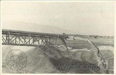 Αποξηραντικά έργα στη λίμνη Γιαννιτσών, εργασίες διευθέτησης της περιφερειακής διώρυγας της λίμνης: το ακραίο τμήμα της σωληνώσεως εκπομπής βυθοκορημάτων όπου διαχωρίζεται η άμμος από το νερό.  Η βυθοκόρηση γίνεται από το σκάφος