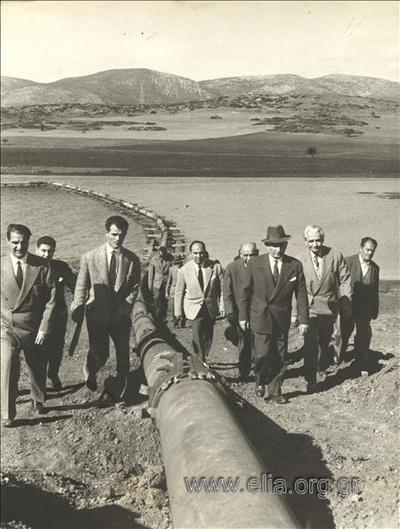 Έργα κατασκευής διαύλου υδροληψίας από τη λίμνη Υλίκη στο αντλιοστάσιο του Μουρικίου: επίσκεψη του υπουργού Δημοσίων Έργων, Σόλωνα Γκίκα, στο χώρο των έργων. Ο υπουργός με συνοδεία ανεβαίνουν στο προστατευτικό ανάχωμα όπου καταλήγει ο σωλήνας μεταφοράςκαι απόρριψης των βυθοκορημάτων.