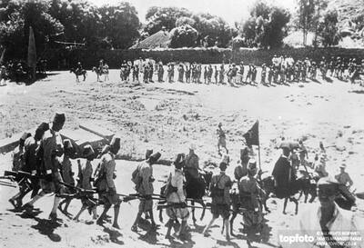Askari troops with flags serving