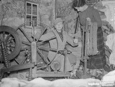 Ann Harding tries spinning wheel